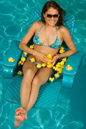 Beautiful woman playing with rubber duckies. photo