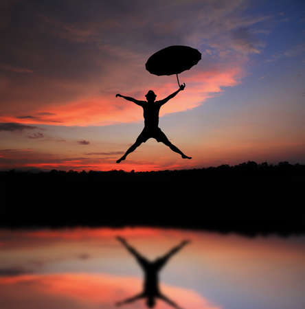 Umbrella man jump and sunset silhouette  Stock Photo