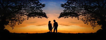 happiness people silhouette on the sunset: The image of two romantic people in love standing at the sunset  Stock Photo