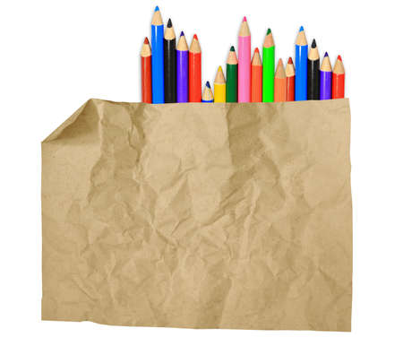 old paper sheet and stack of colored pencils on white background  photo