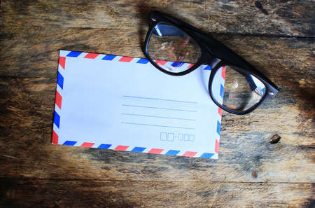 Envelope and glasses on wooden table. photo
