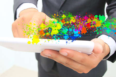hands touching tablet with paint splash photo
