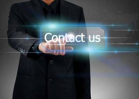 find us: businessman pushing on contact us button. Stock Photo
