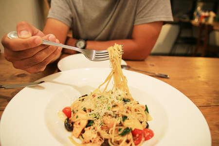 man eating: A man eating spaghetti.