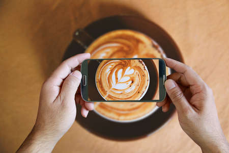 Hand holding smartphone taking photo of coffee. from above,topview