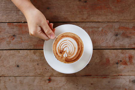 coffee table: woman hand holding cup of coffee while resting in the cafe,top view Stock Photo