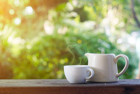 tea table: Cup of tea and teapot on wooden table                  Stock Photo
