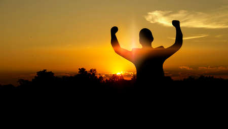 Silhouette of businessman raising arms in sunset. Business succes concept