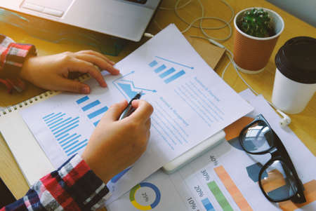 financial graph: Businesswoman analysis financial paperwork and reports graph                          Stock Photo
