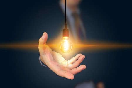 energy work: businessman holding light bulb. creative business strategy concept