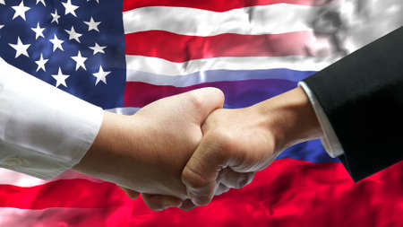 Businessman shake hand over United States of America and Russia flag. Фото со стока