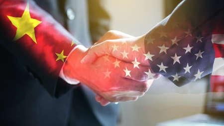 Uomo d'affari stringe la mano sulla bandiera degli Stati Uniti d'America e della Cina. Archivio Fotografico