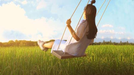 Girl on swing in sunlight.