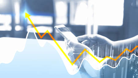 Businessman working with smartphone. Business graph background Фото со стока