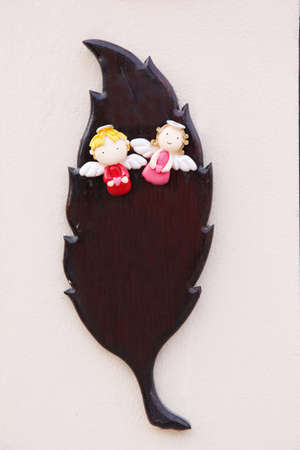 Little angel boy and girl on brown wood leaf photo