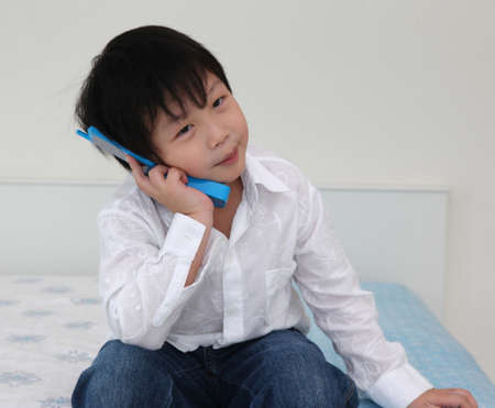 Asian little boy playing phone on bed room photo