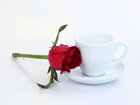Cup of coffee with red rose, isolated on white  photo