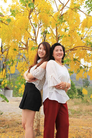 Portrait of two woman : Mother and daughter standing under beautiful tree photo