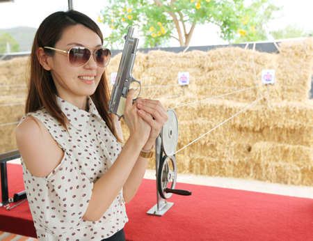 Young beautiful woman weared sunglasses holding a handgun at shooting gallery photo
