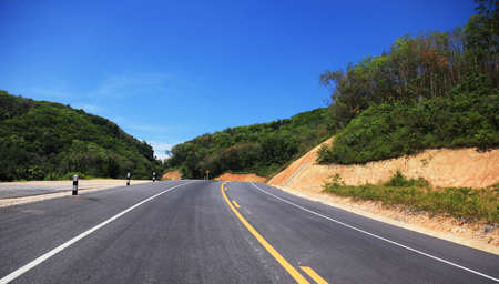 Highway along mountain and blue sky photo