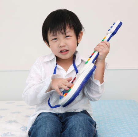 Asian little boy playing guitar photo