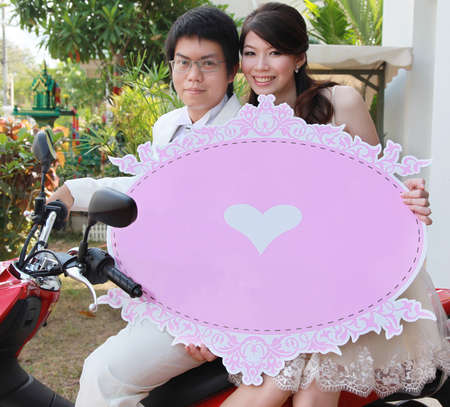 Betrothed sit on motorcycle and carry pink backdrop. photo