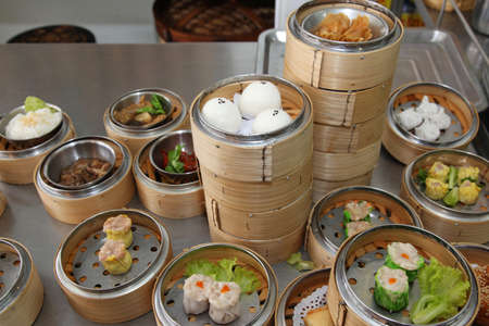 dim sum: Steamed stuff bun and many chinese steamed dimsum in bamboo containers traditional cuisine  Stock Photo