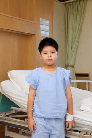 ban aid: Young boy wear patient suit standing  in front of hospital bed Stock Photo