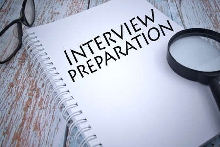 Selective focus image of magnifying glass with spectacle and INTERVIEW PREPARATION wording. Business concept