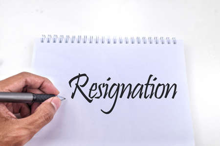 Selective focus image of a person hand holding pen with Resignation wording. Business and economy concept Imagens