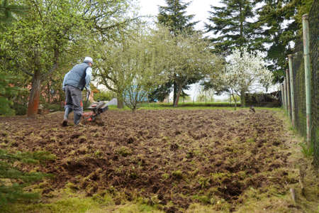 Man plows the ground with a motor cultivator. A farmer ploughs the soil using a petrol cultivator.