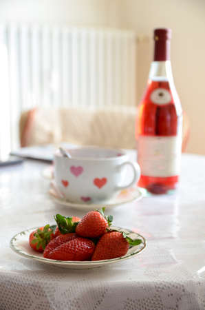 glass of pink champagne with strawberries on the table