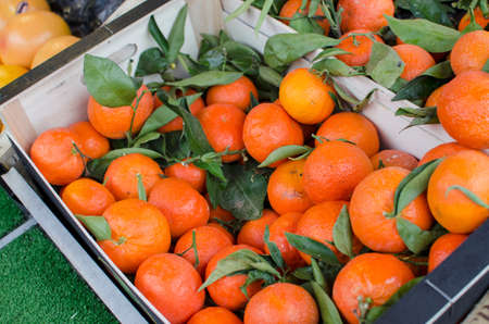The wooden box full of fresh ripe mandarins top view, on market background