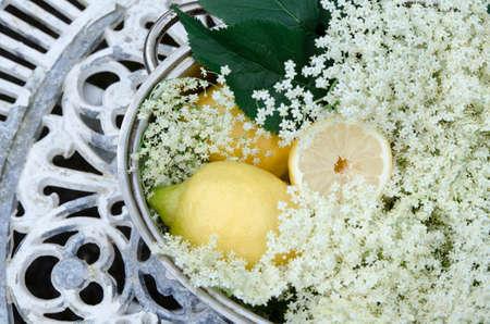 preparation of elderberry juice ingredients of elderflower and lemon, preparation on the old table