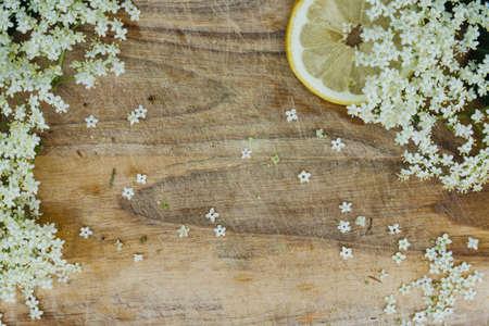 preparation of elderberry juice, ingredients of elderflower and lemon, preparation on the old table Фото со стока