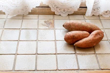 Sweet potato on the light tiles near the window, retro kitchen 免版税图像