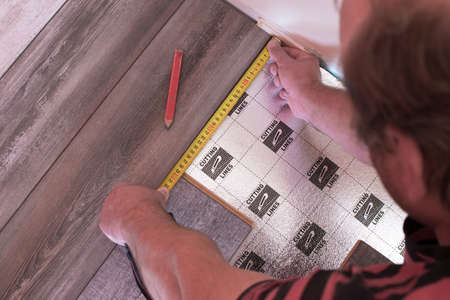laying a floating floor, including sound insulation, man measures the distance by the meter Stockfoto