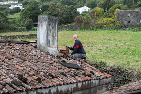 old roof and view of old tiles, roof before renovation, before repair, man on the roof near the chimney