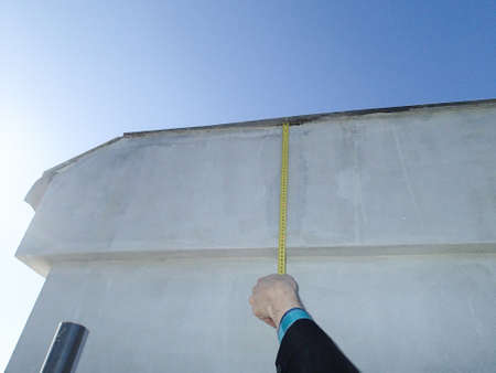 Roofer holding a tape measure and spirit level in his hands over newly installed tiles on a new build wooden house Banco de Imagens