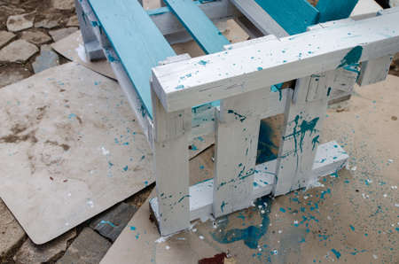 freshly painted bench made of pallets, colorful splashes, protective papers