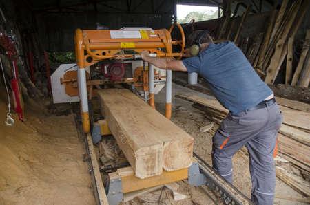 man operates a log band saw. Hard work