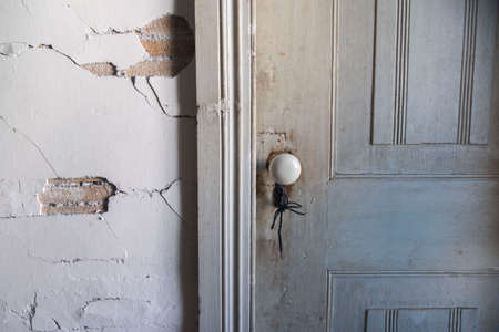 the old wall of the house from which part of the plaster has fallen off and destroyed, close-up of an old building , closed white wooden door