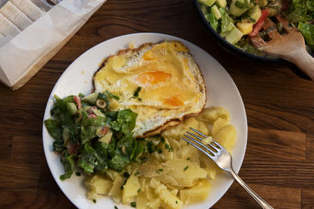 lunch on a plate on a wooden table, potatoes with eggs and salad, close up