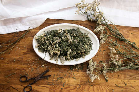 collection of herbs, dried yarrow on a wooden brown background, kitchen board, 免版税图像