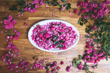 ceramic white bowl with pink roses closeup, view from above