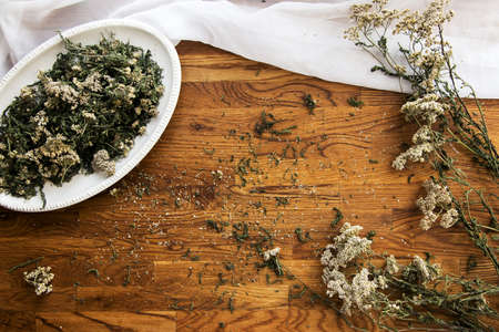 collection of herbs, dried yarrow on a wooden brown background, kitchen board, close up