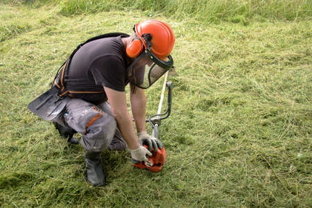 Landscapers men gardeners cutting grass with string lawn trimmers, summer time