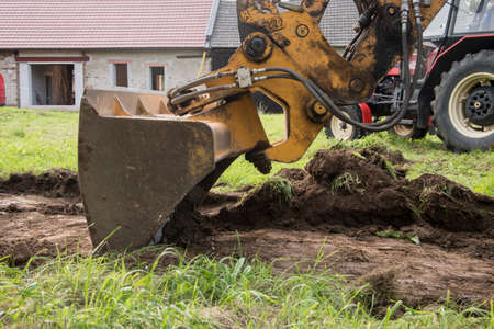 demarcation of a new building on topsoil before the construction of a family house begins, heavy machine 免版税图像