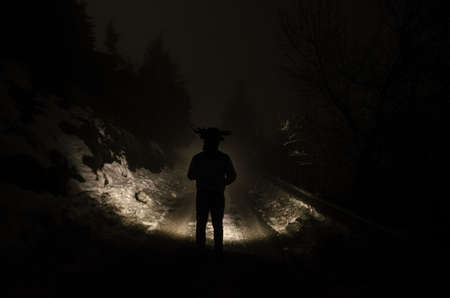 man walking in spooky forest at night, winter time