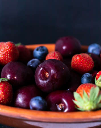 Blueberry, Strawberry and cherry in faience bowl with fruit closeup